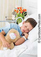 Boy with teddy bear sleeping in hospital