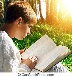 Boy with the Book outdoor - Teenage Boy sit in the Forest...
