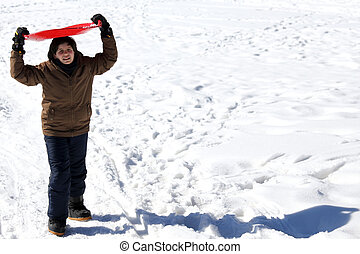boy with the Red Snow sledge in winter