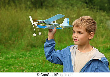 boy with toy airplane in hands outdoor