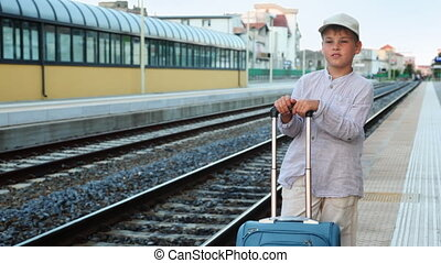 Boy with travel bag stands and smiles on train station near railway lines