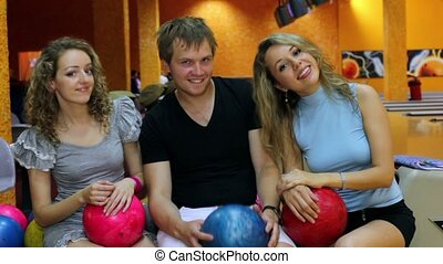 Boy with two girls sit and sways with balls in bowling club