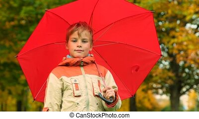 boy with umbrella stands in autumn park
