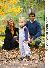 boy with untied lace and parents in autumn park