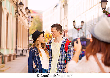 Boy with woman stand close and girl shooting them