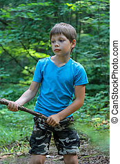 Boy with wooden stick in summer forest park