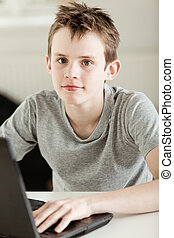 Boy Working on his Laptop Looking at Camera