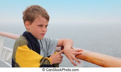 boy wrapped in plaid stands on deck and admire seascape