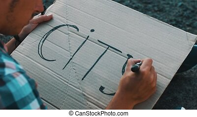 Boy write word city on cardboard plate by marker. Sitting at...