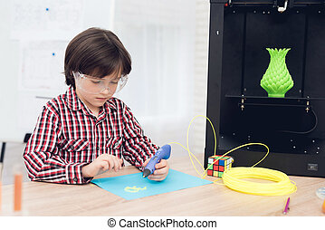 Boy writes by 3d pen during a lesson in class.