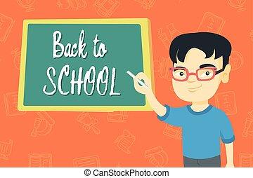 Boy writing text back to school on the blackboard.