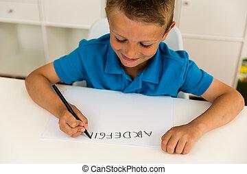 Boy writing the ABC alphabet