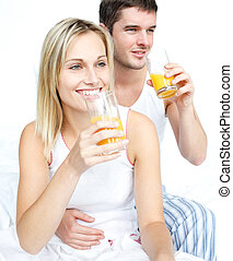 Boyfriend and girlfriend drinking orange juice in bed