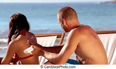 Boyfriend applying cream to his girlfriend