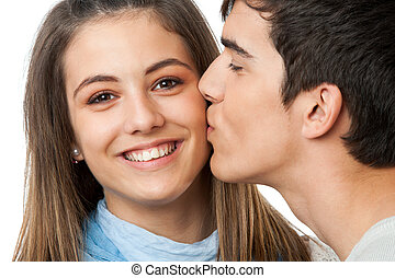 Close up portrait of boyfriend kissing girlfriend on cheek. Isolated on white.