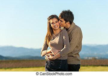 Boyfriend kissing girlfriend on cheek outdoors.