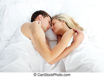Boyfriend looking at his girlfriend sleeping in bed