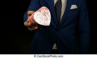 Boyfriend offers heart shaped gift box to his lover