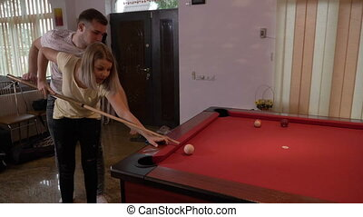 Boyfriend teaching his girlfriend to play pool flirting and having fun