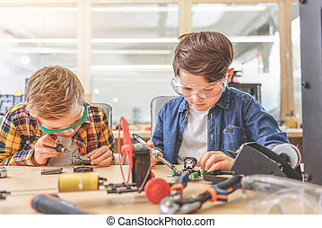 Boys absorbedly creating technical toys