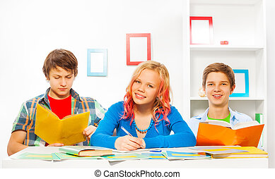 Boys and girl do homework together at home