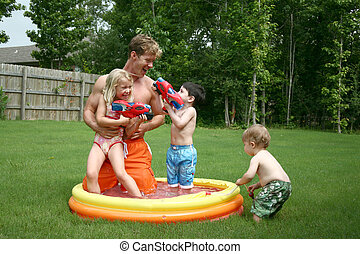 Boys and girl play with dad in the kiddie pool
