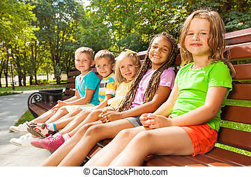 Boys and girls sitting on the bench in park