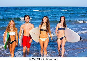 boys and girls teen surfers coming out from the beach