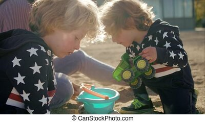 Boys and mom are playing with a toys on the beach.