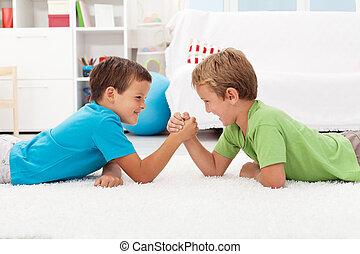 Boys arm wrestling in the kids room
