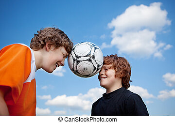 Boys Balancing Soccer Ball With Heads Against Sky