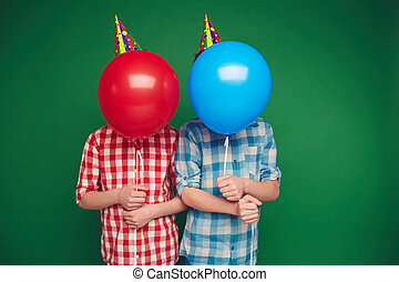 Boys behind balloons - Two boys hiding behind red and blue...