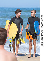 boys carry bodyboards on the shore of beache