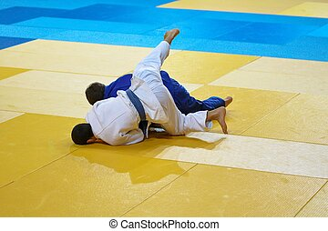 Boys compete in Judo - Two boys judoka in kimono compete on...