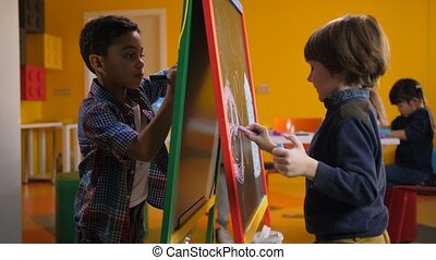 Boys drawing with colorful chalks on easel board - Engrossed...
