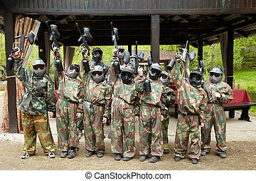 Boys dressed in camouflage stand in a row on a paintball...