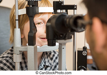 Boy's Eyes Being Examined By Slit Lamp - Preadolescent boy's...