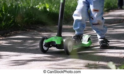 Boy's feet riding mini scooter, kick scooter in the park in...