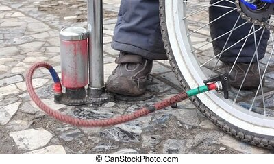 boy\'s foot on air-pump, pumping bicycle wheel