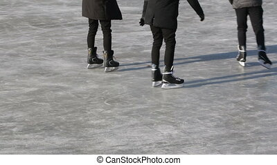 Boys friends skate on the rink during the winter Christmas...