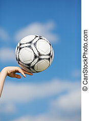 Boy's Hand Balancing Soccer Ball Against Sky