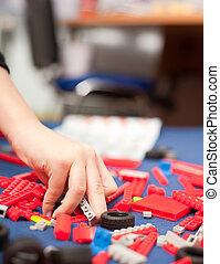 Boy\'s hand picking plastic toys