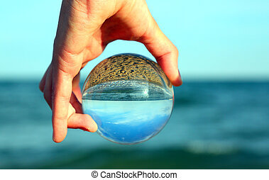 hand with big crystal ball by the ocean in summer
