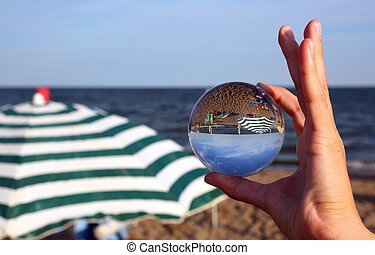 hand with big crystal ball on the beach with parasol by the sea