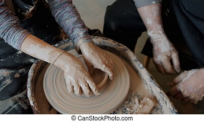 Boy's hands making bowl from clay working with spinning ...