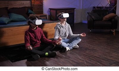 Modern diverse teenagers in VR headsets practicing yoga in virtual reality while sitting on floor in lotus position. Advanced mixed race friends spending free time learning zen in cyberspace
