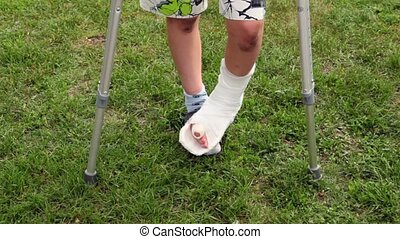 Boys injured leg with broken finger, closeup view on grass