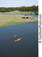 Boys kayaking. - Aerial of two teenage boys kayaking through...