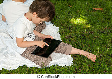 boys looking at the tablet in nature in the park