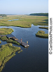 Aerial view of two teenage boys fishing from dock in marshy lowlands of Bald Head Island, North Carolina.